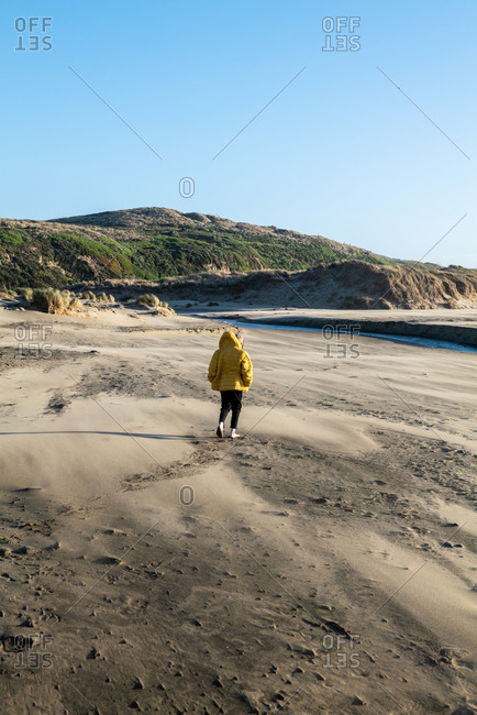 Boy walks on sandy beach toward fresh water stream leading to ocean