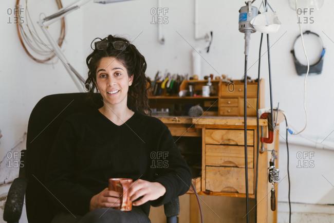 Candid environmental portrait of California jeweler sitting in studio