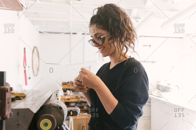 Female jeweler smiling while working at grinder at home studio space