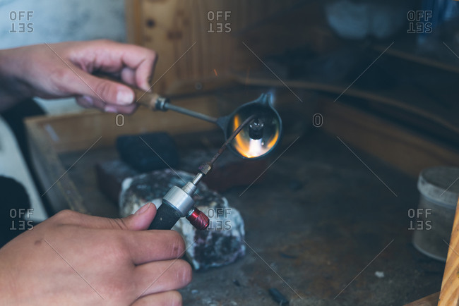 Detail of hands using blowtorch to melt fine metal while crafting