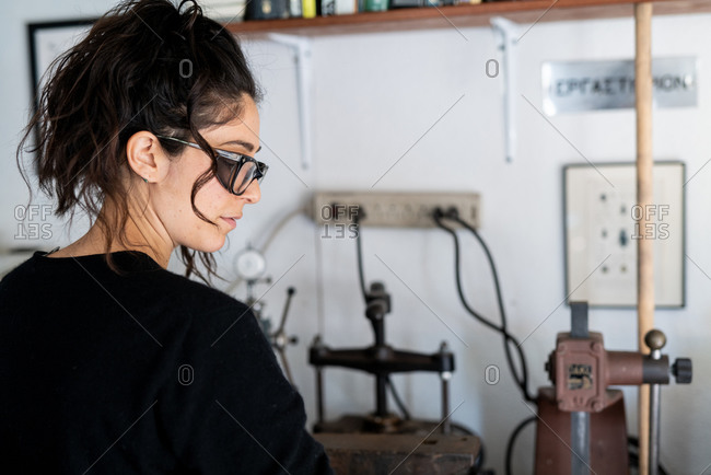 Profile portrait of female jeweler working in well lit home studio