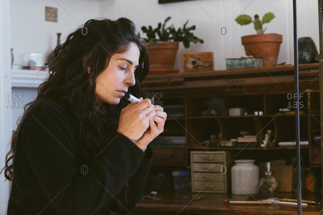 Profile portrait of female artist working on tiny jewelry in studio