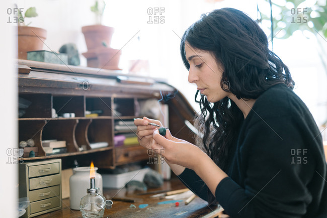 Portrait of female jeweler working at home studio with small tools