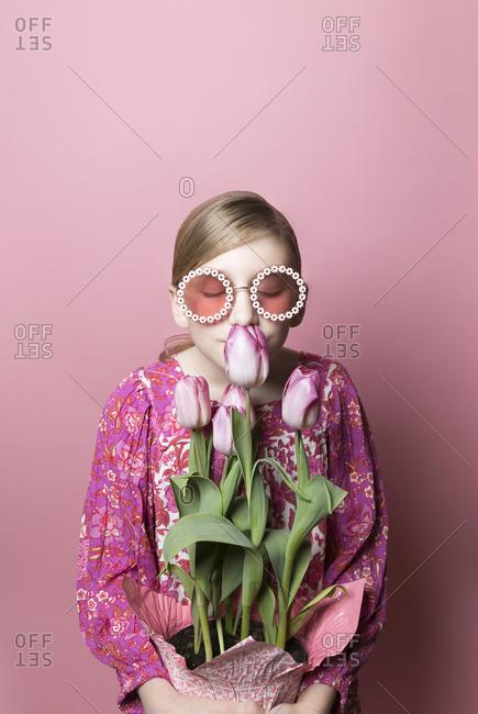 Blonde tween girl in sunglasses smells pink tulips on pink background
