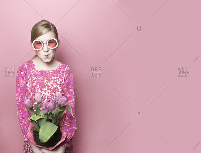 Mod blonde tween fair skin with pink tulips, pink dress, pink backdrop