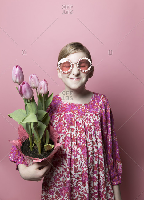 Mod, quirky girl, fair skin, holding pink tulips on pink backdrop