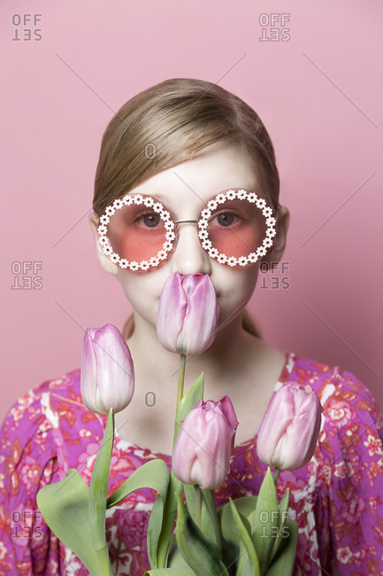 Close up of mod tween girl smelling pink tulips on pink background
