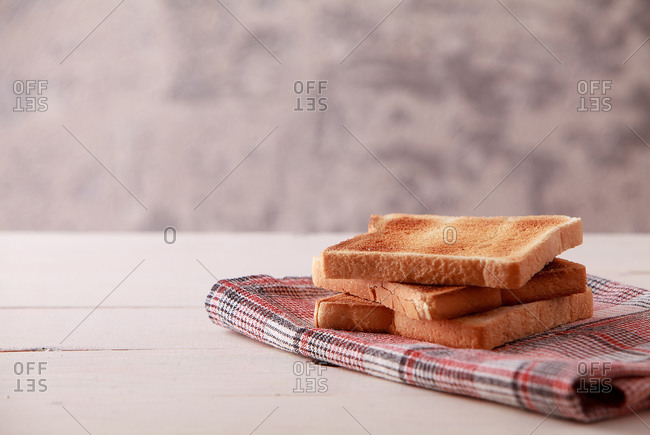 A stack of sliced bread toasts on white wooden background