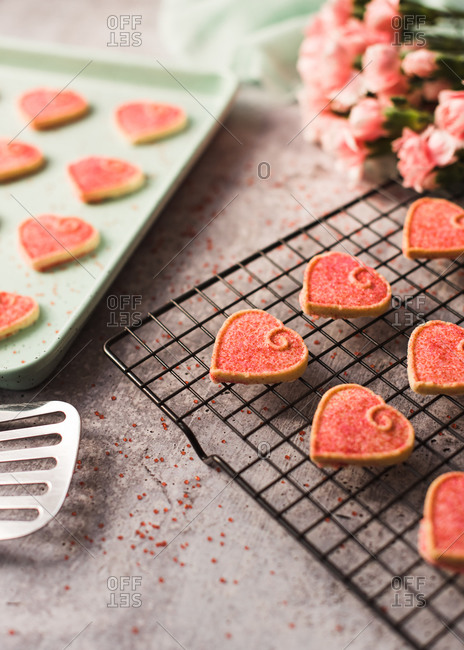 Close up of Valentine\'s day heart cookies cooling on a pan and rack.