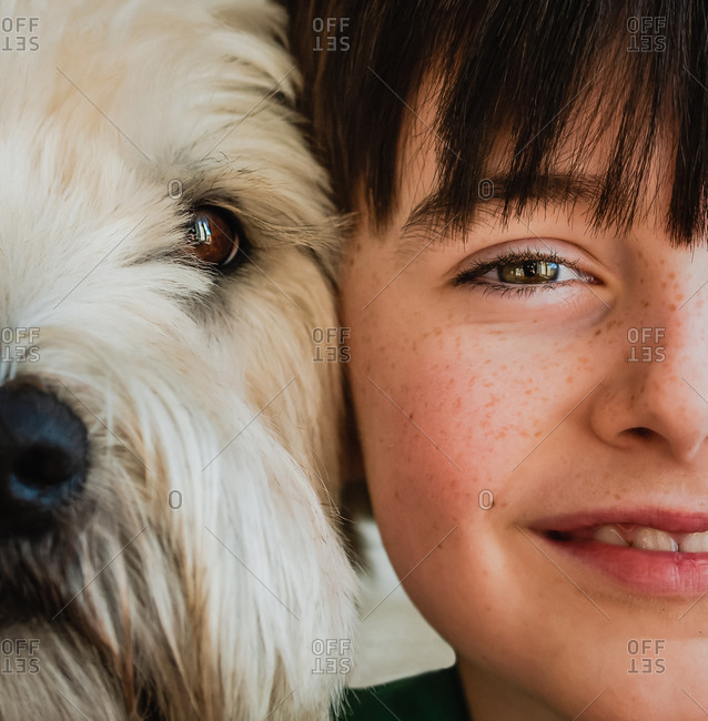 Close up of half of the faces of boy and his dog with heads together.