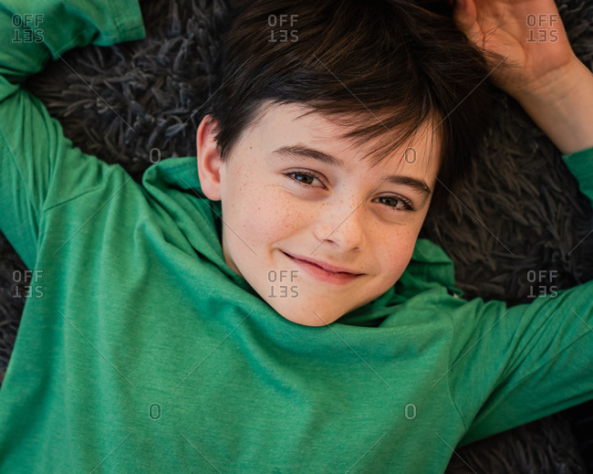Looking down at the face of a young happy boy laying on a pillow.