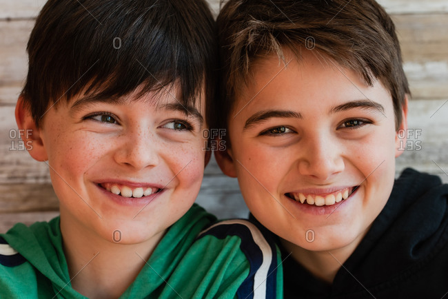 Close up of two smiling boys with their heads close together.