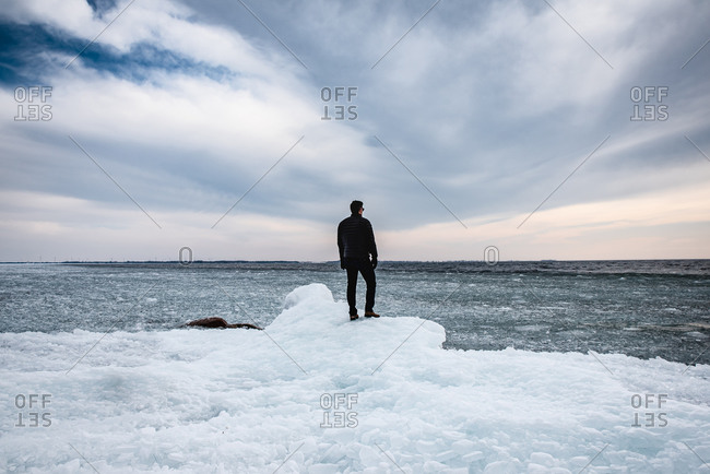 Man standing on an icy shoreline of a lake looking into the distance.