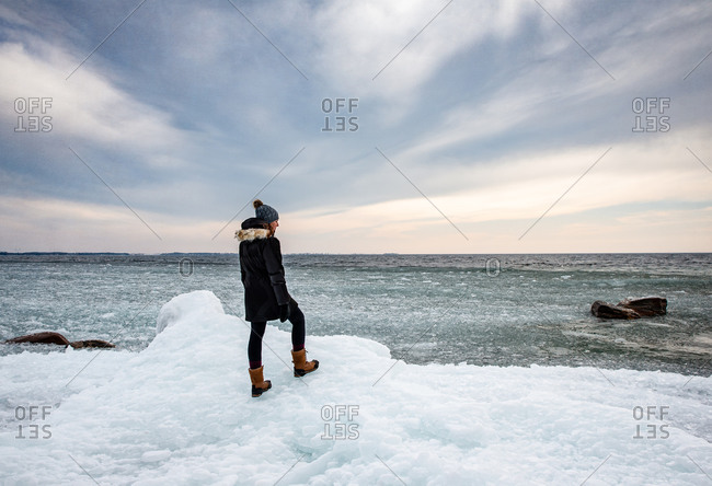 Woman standing on icy shoreline of a lake looking into the distance.