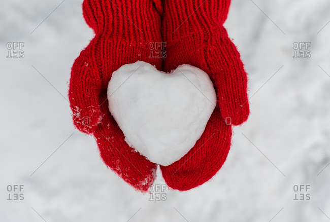 Close up of two hands in red mittens holding heart shaped snowball.