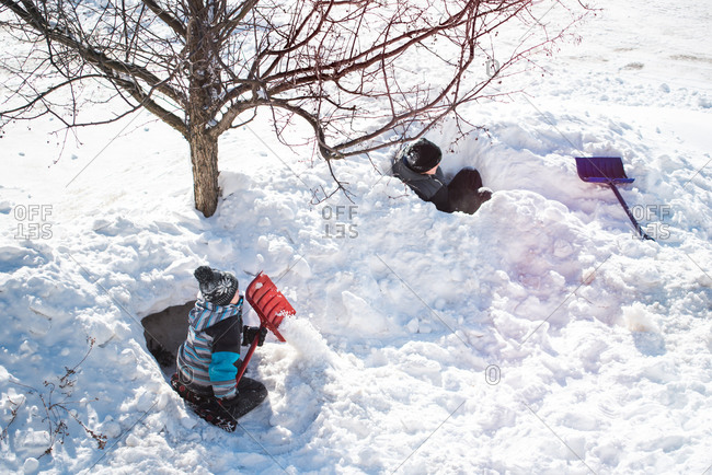 Two boys building snow forts with shovels on a sunny winter day.