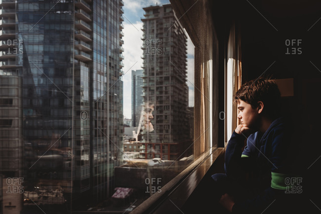 Tween boy looking out a window at tall buildings of the city outside.