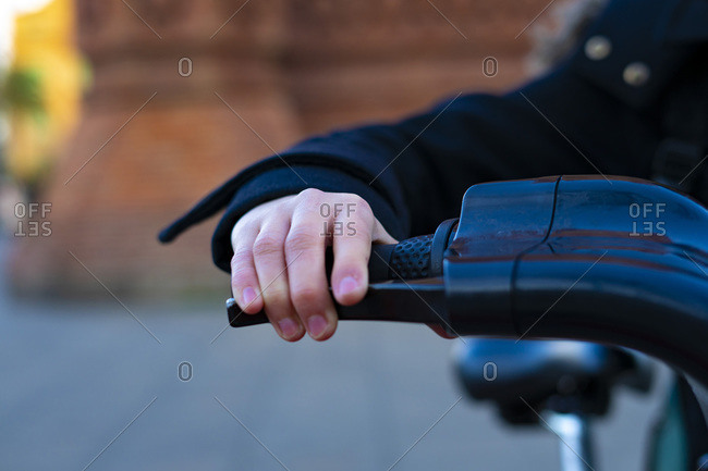 Hand taking the handlebars of a bicycle.