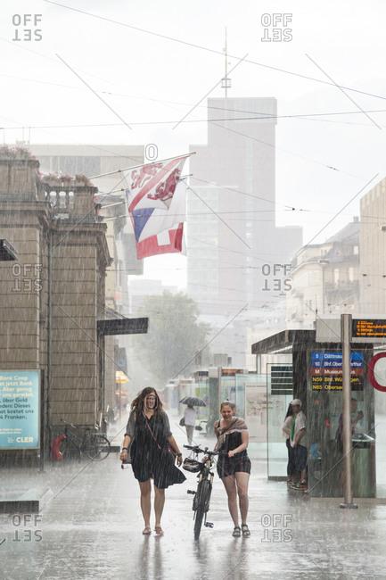 Winterthur, Switzerland - June 2, 2017: Women walk with bicycle through rainstorm