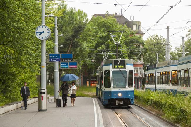 Zurich, Switzerland - June 2, 2017: People catch incoming tram at Milchbuck station