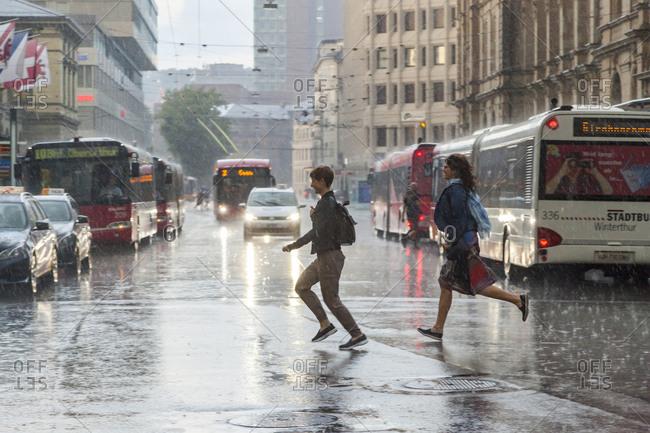 Winterthur, Switzerland - June 2, 2017: Women run across street in heavy rainstorm