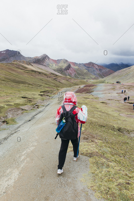 A young woman is hiking to the famous Rainbow Mountain in Peru
