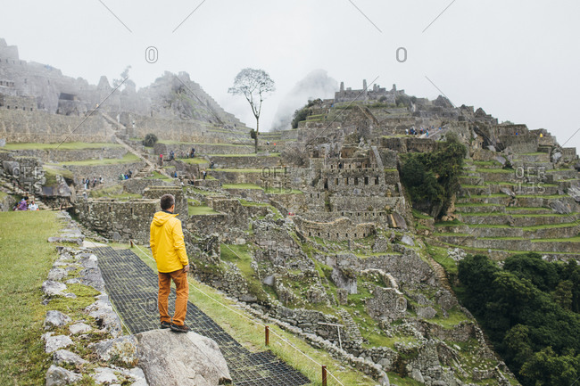A man in a yellow jacket is standing near ruins of Machu Picchu, Peru