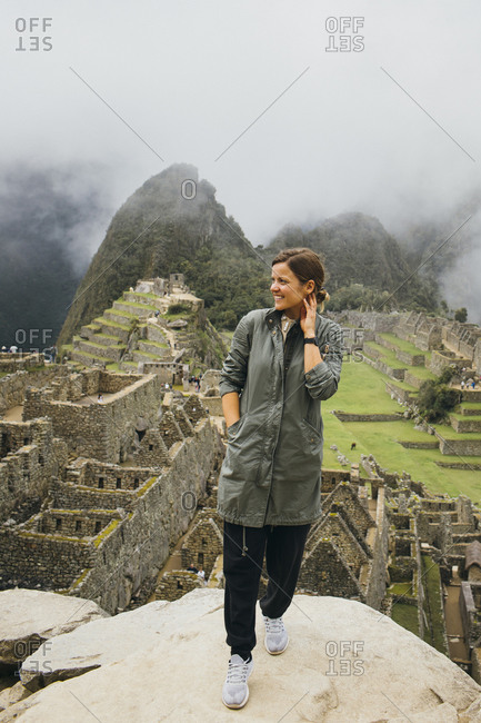 A young woman is standing near ruins of Machu Picchu, Peru