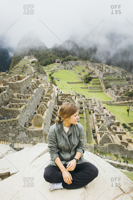 A young woman is sitting near ruins of Machu Picchu, Peru