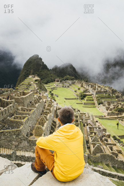 A man in a yellow jacket is sitting near ruins of Machu Picchu, Peru