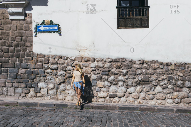 A young woman is standing near a white wall in Cusco, Peru