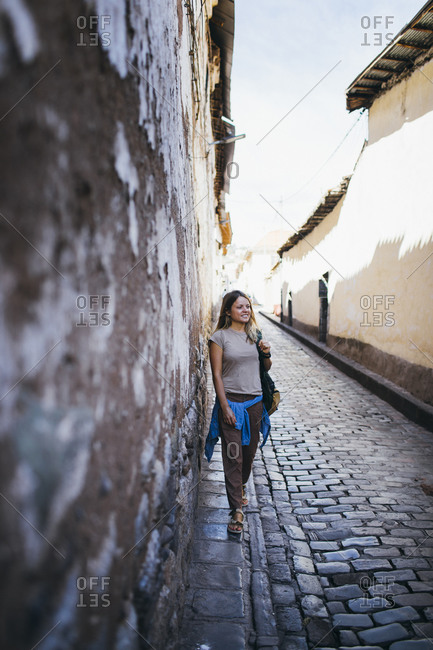 A young woman is standing near an old wall in Cusco, Peru