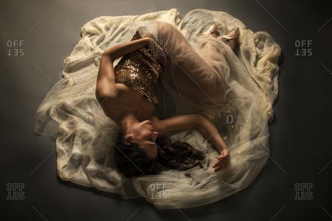 Young elegant ballet dancer on the floor on a veil