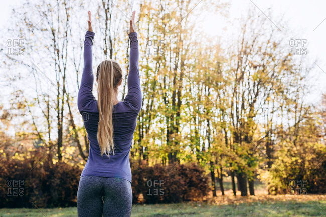 Woman in the forest Back view Outdoor activity Young attractive woman doing exercise working outdoors. Rear view