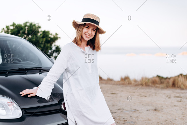 Romantic, dreamy girl with red hair is cute standing in the car