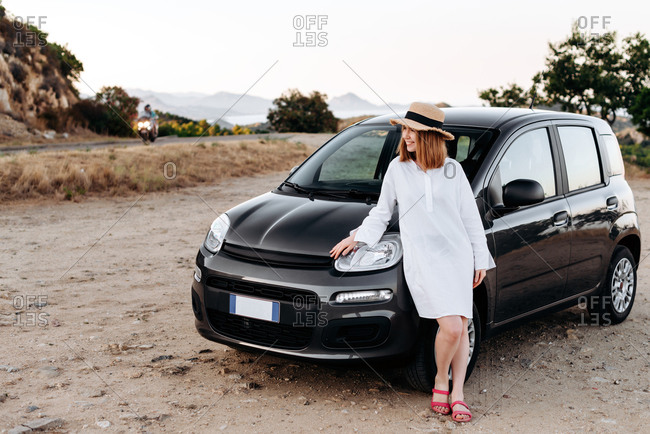 Cute, charming girl in a straw hat poses around a black car on the roadside.