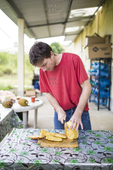Young man cutting fresh, organic pineapple on wood cutting board.