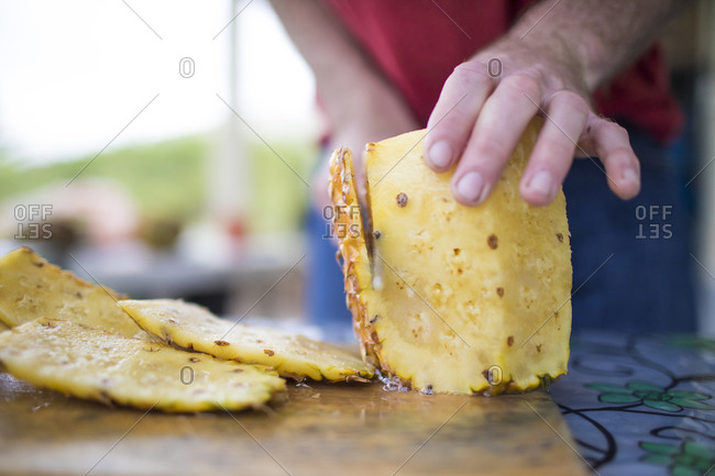 Detailed view of man slicing fresh pineapple outdoors