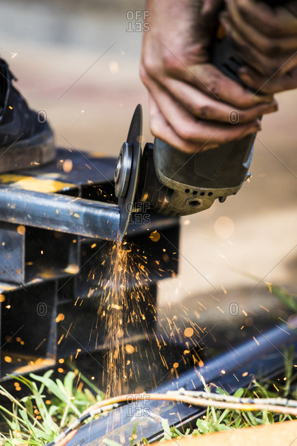 Close-up of skilled worker using angle grinder to cut steel.