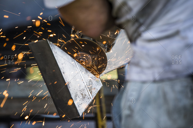 Close-up of worker using angle grinder in a factory