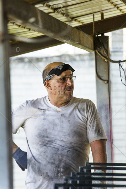 Portrait of a metal worker standing in workshop with dirty shirt.