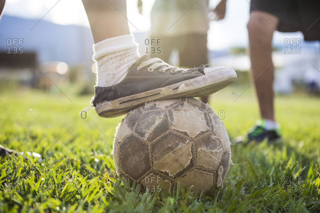 Soccer (football) player places old shoe on torn soccer ball.