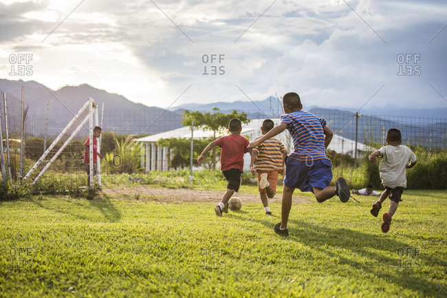 Monjas, Guatemala - October 24, 2019: Group of friends playing soccer on grass field before sunset.