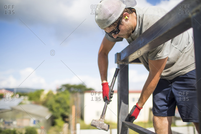 Construction worker using hammer to build steel railing on roof.
