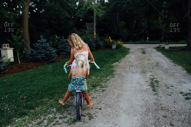 Two girls riding a bike down a driveway in the summer