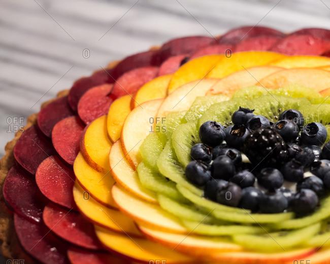 Rainbow Fruit Tart on Marble Pastry Board
