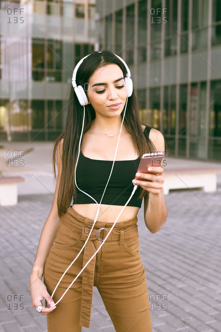 Young girl of Arab ethnicity dressed listening to music