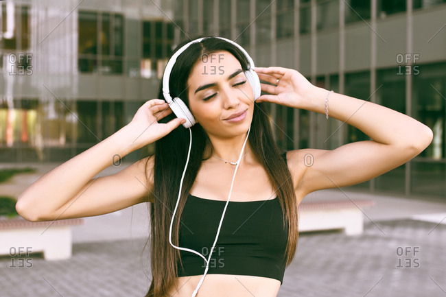 Young girl of Arab ethnicity closes her eyes while listening to music