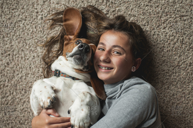 Tween girl posing with her basset hound dog while laying on the carpet