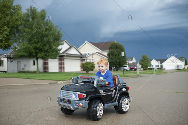 Young boy drives electric toy car down neighborhood street